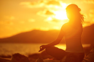 42202422 - yoga in the beach. woman meditating in lotus pose on the beach at sunset